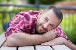 An image of a bearded handsome man lying on a bench