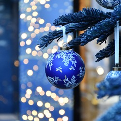 An image of a blue round Christmas-tree decoration with a floral motif and two white round Christmas-tree decorations nearby, hanging on a Christmas tree, on a background of lights with Bukeh effect