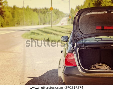 An image of a car trunk open waiting for help in side of the road. Image has a vintage effect.