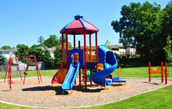 An image of a colorful children's playground in  suburban area.