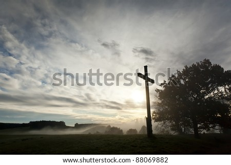 An image of a dramatic sky and a cross - stock photo