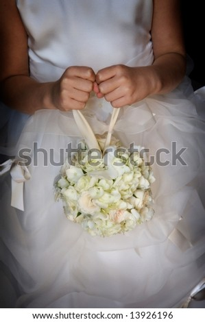 An image of a flower girl holding her floral bouquet