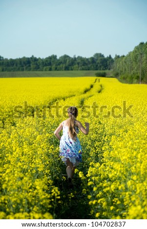 An image of a girl running in the yellow field