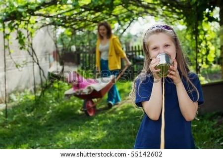 An image of a girl with a toy-telephone