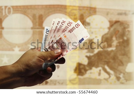 An image of a hand holding Euro currency with the continent of Europe as background.
