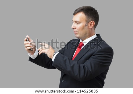 An image of a handsome business man and his mobile phone
