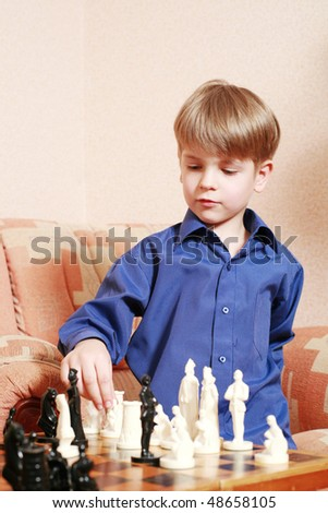 An image of a little boy playing chess