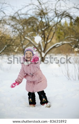 An image of a little girl playing snowballs