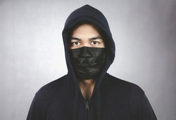 An image of a man in a hood or a jig on a dark gray background with a black mask covering his mouth and nose.