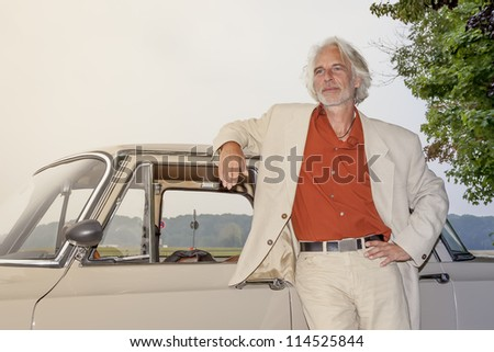 An image of a man in front of his car