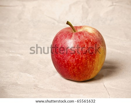 An image of a nice red apple on grunged paper background