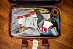 An image of a packed suit case on a wooden floor of a South African man who has received his covid vaccine and has a certified travel certificate along with his passport and flight boarding pass
