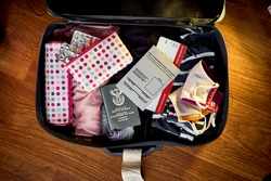An image of a packed suit case on a wooden floor of a South African woman who has received her covid vaccine and has a certified travel certificate along with her passport and flight boarding pass