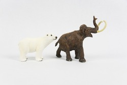 An image of a polar bear and a woolly mammoth figurines, isolated on a white background.