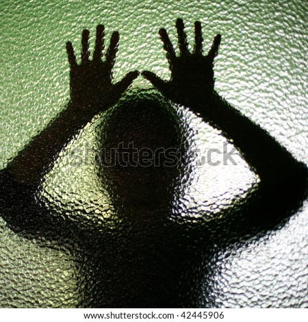 An image of a silhouette behind glass