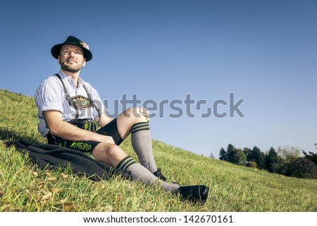 Photo of An image of a traditional bavarian man relaxing in the grass