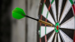 An image of a typical darts game with dart in the bullseye