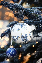An image of a white round Christmas-tree decoration with a floral motif and a blue round Christmas-tree decoration nearby, hanging on a Christmas tree, on a background of lights with Bukeh effect