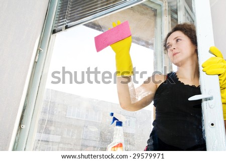 An image of a woman washing the window