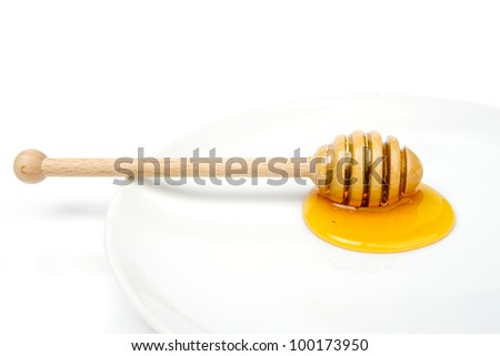 An image of a wooden dipper with honey on it