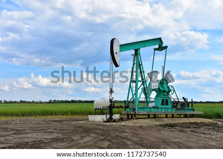 An image of a working oil well pump jack on a cloudy day.  Stockfoto ©