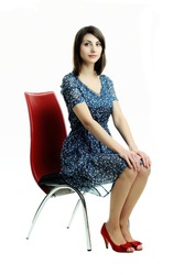 An image of a young girl sitting on a chair