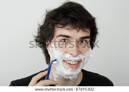 An image of a young handsome man shaving