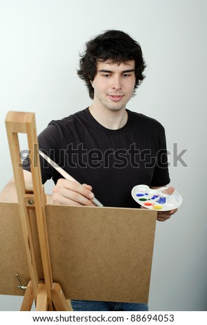 An image of a young man drawing a picture