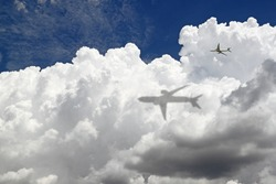 An image of an airplane flying through a cloud casting a big shadow on it.