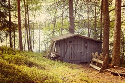 An image of an An old shed which is built for storing wood and tools in the countryside of Finland. Image has a vintage effect applied.