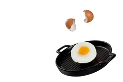 An image of an egg being cracked, falling, and transforming to fried egg on a black ceramic serving pan. Levitation food concept.