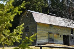 An image of an old abandoned barn with faded yellow paint.