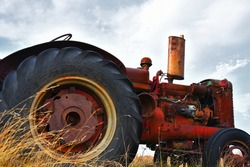 An image of an old antique farm tractor that has fallen into disrepair.