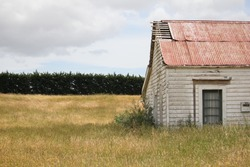 An image of an old derelict farm house set on a farmland and surrounded by dry uncut grass.