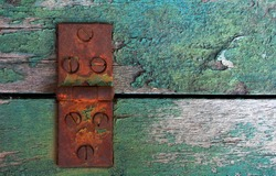 An image of an old rusted metal door hinge on weathered green wood.