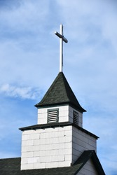 An image of an old wooden cross on a church steeple.