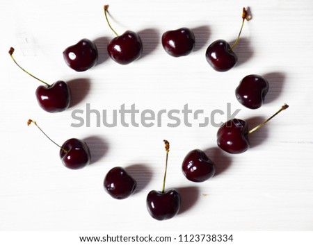 An image of eleven cherries: six cherries with fruit stalks and five without fruit stalks arranged in the heart form on a white wooden surface #1123738334