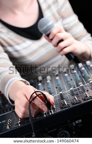 An image of female hand connecting a cable to an audio mixing board and holding a microphone.