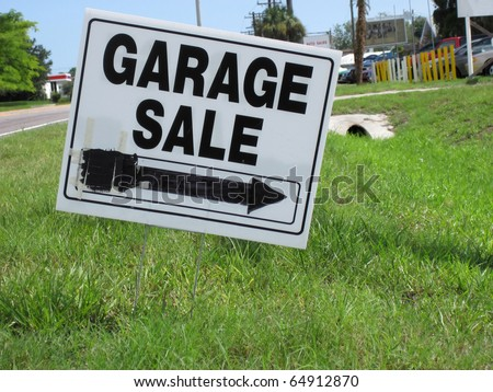 an image of garage sale sign on green grass - stock photo