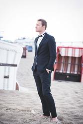 an image of groom posing on the beach