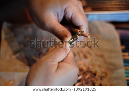An Image of Hands Sharpening Pencil. Woman sharpens pencil with knife. Hands of close up