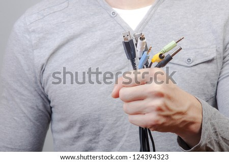 An image of man holding many cables with plug and scissors in other hand