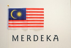 An image of national flag of Malaysia with 'Merdeka' isolated in white. Merdeka mean independence ans and Malaysia already independence since 1957. Selective focus