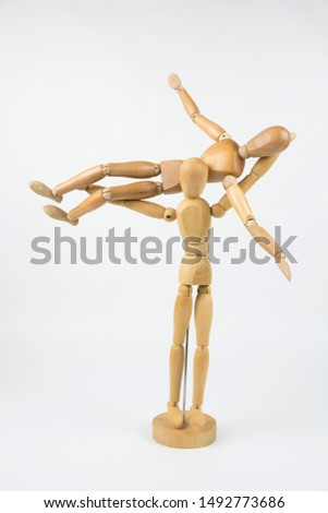 An image of one wooden mannequin holding another mannequin up in the air with its arms. The mannequins could be dancing, performing acrobatics, or cheerleading.