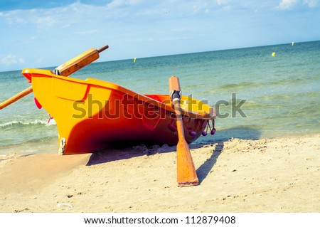 An image of orange rescue boat on the beach of baltic sea