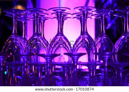 An image of purple hued stacked wine glasses - stock photo