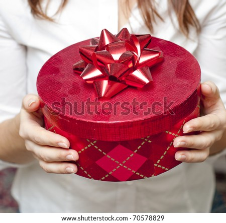 an image of red box holding in hand of young girl