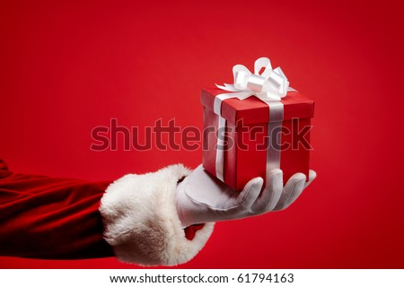 An image of Santa?s hand holding a gift box against red background