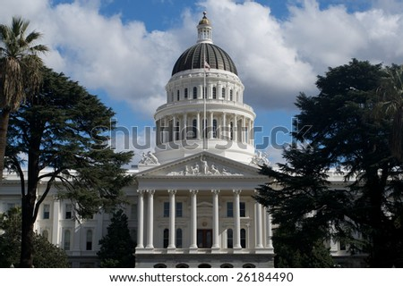 an image of the California State Capital Building from a distance bordered by trees and a blue sky with grey and white clouds