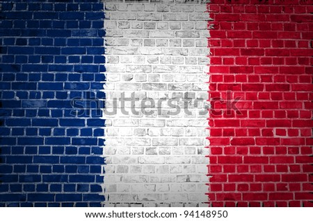 An image of the France flag painted on a brick wall in an urban location